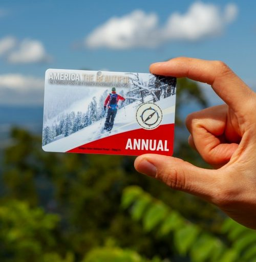 A person holding the National Parks annual pass