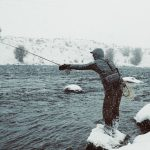 A man fly fishing in the snow in the Gallatin River