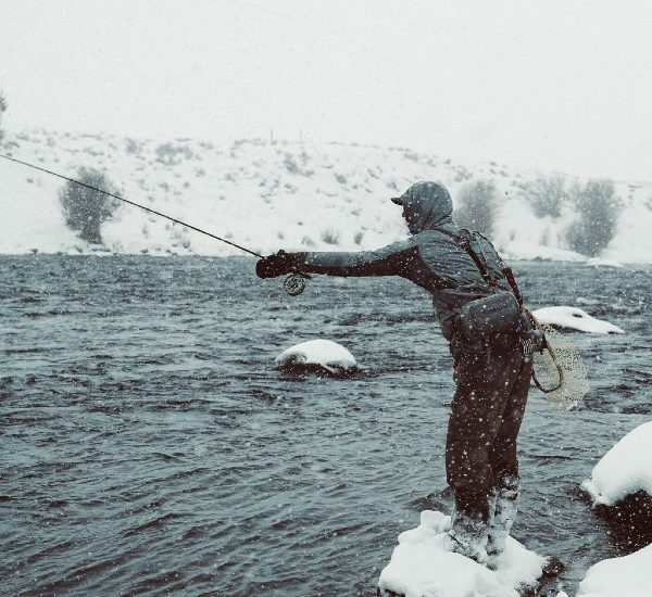 A man fly fishing in the snow in the Gallatin River, one of the best things to do in Big Sky Montana in winter or summer