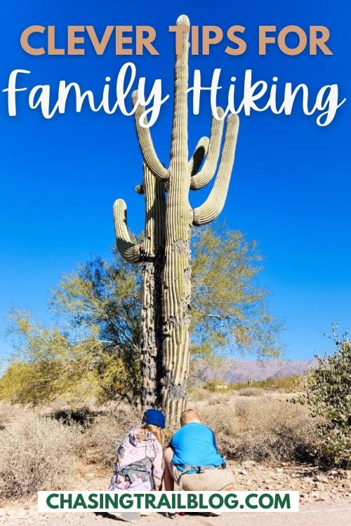 """Two children kneeling in front of a saguaro cactus in the desert on a sunny, cloudless day and the words """"Clever tips for family hiking"""" and """"chasingtrailblog.com"""""""