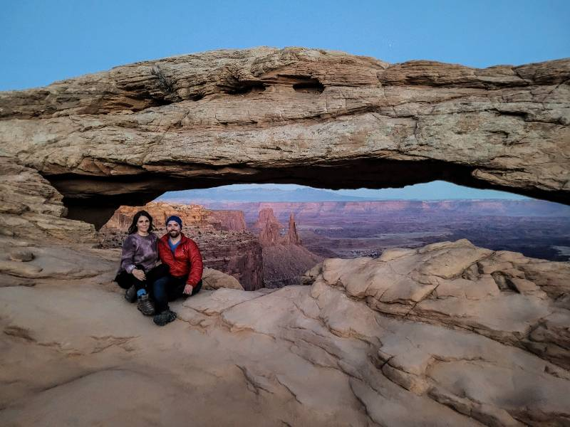 Two people sitting near Mesa Arch, one of the best hikes in Canyonlands