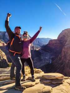 A man and woman on the summit of Angels Landing in winter