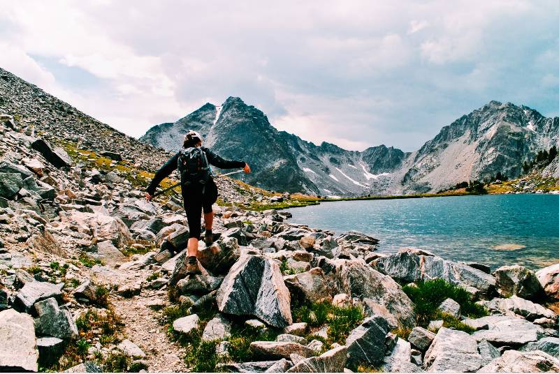 A woman hiking near the shore of Summit Lake, one of the best hikes in Big Sky Montana