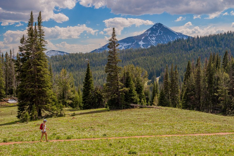 A woman hiking in Big Sky Montana across a meadow with Lone Peak in the background
