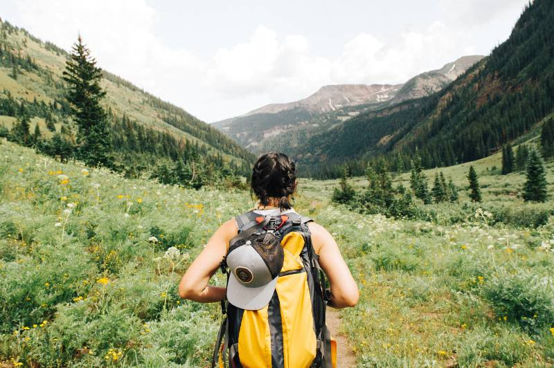 A woman hiking in the mountains and carrying a yellow hydration backpack