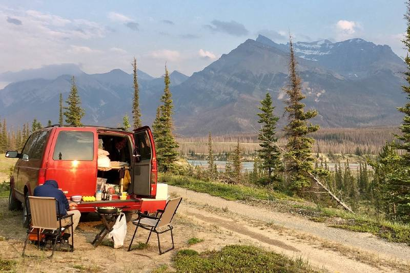 A man preparing a meal outside a campervan with mountains in the background