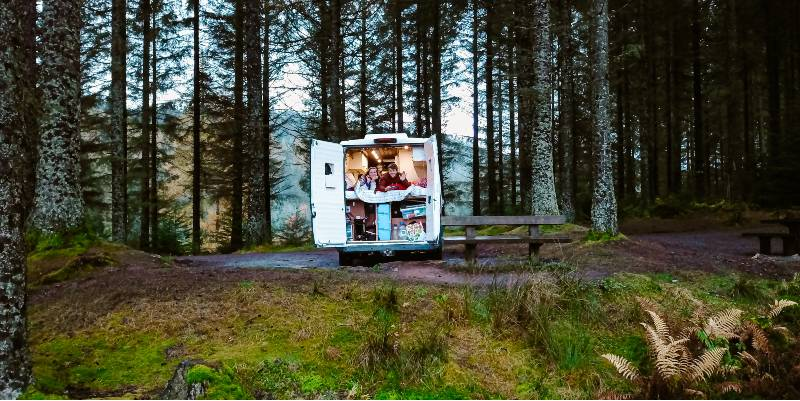 Two people in the back of a campervan in a forest. One of the best cross country road trip tips is to travel and boondock in a campervan.