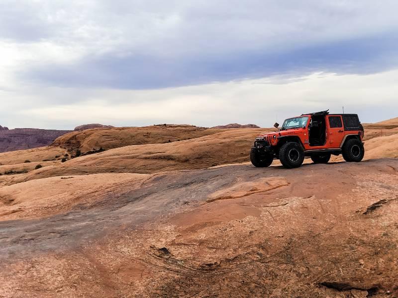 An orange Jeep offroading in Moab Utah