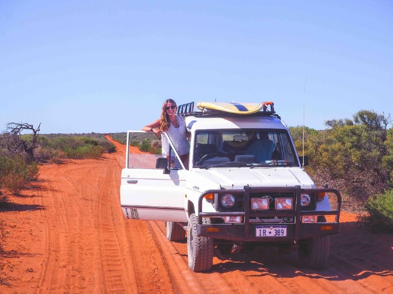 A woman leaning out of an off-road vehicle in Australia with some of her road trip essentials