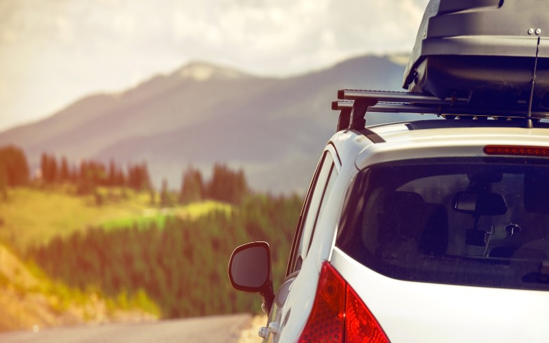 A mountain view and a vehicle with a roof rack, considered one of the top road trip essentials