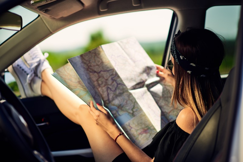 A woman reading a paper map in a vehicle, which is one of the best cross country road trip tips