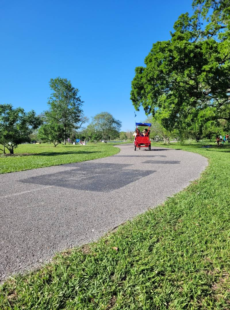 A red surrey in City Park, which is one of the best New Orleans outdoor activities to enjoy