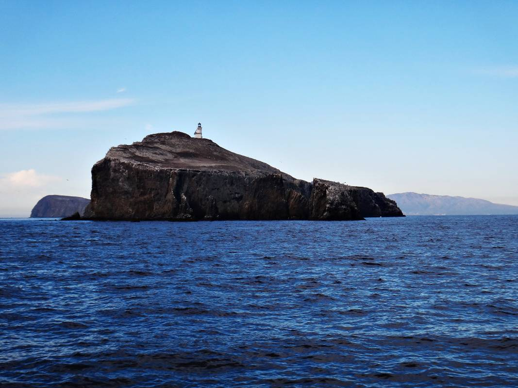 A lighthouse on a rocky island in Channel Islands National Park, one of the top must-see national parks in the US