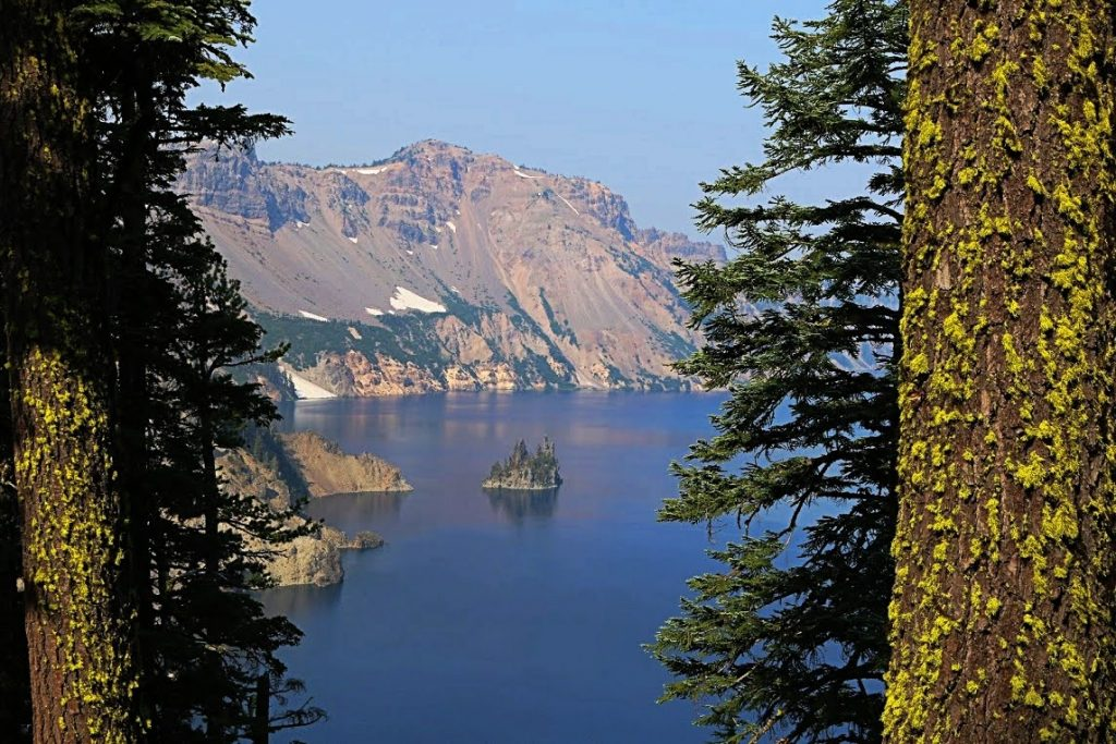 A view of Crater Lake between two trees at Crater Lake National Park, one of the most underrated national parks in the US
