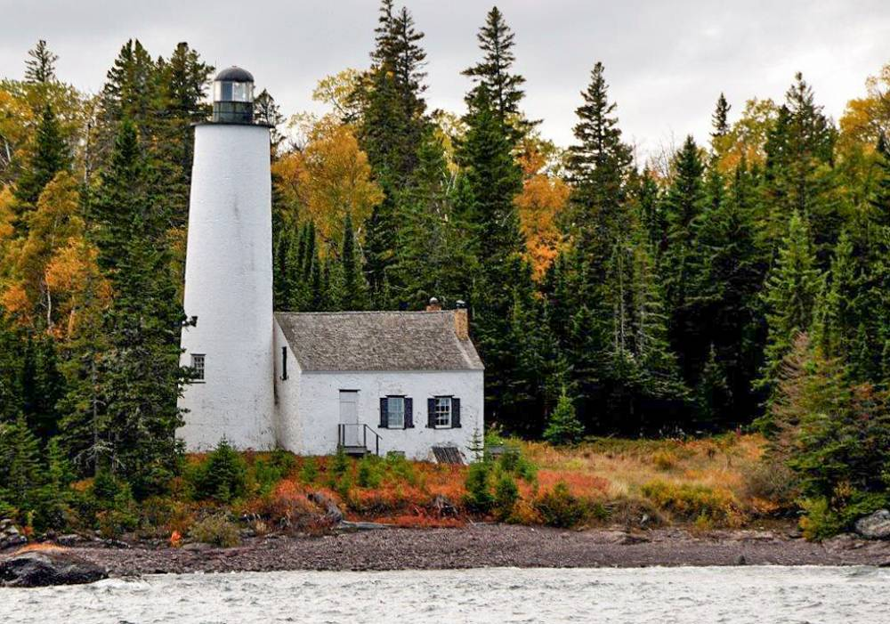 Rock Harbor Lighthouse with trees changing colors during the fall in Isle Royale, an underrated national park in Michigan
