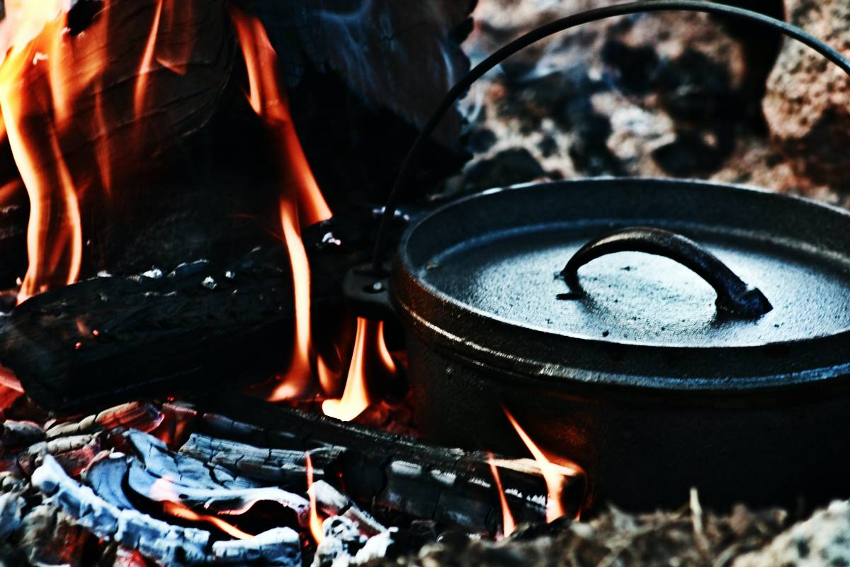 A close-up of a campfire with a cast iron Dutch oven nestled into the embers
