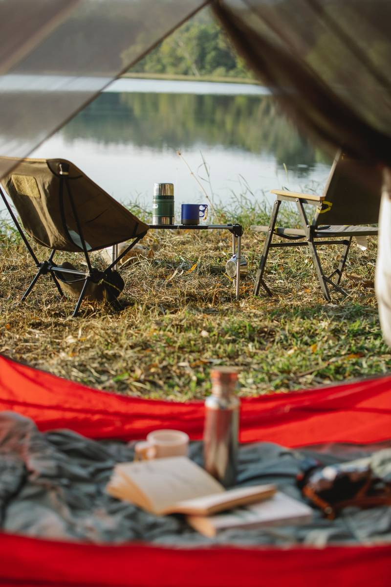 Two chairs near a folding table with a coffee cup and thermos sitting on top, all camping must haves, and a tent and book in the foreground.