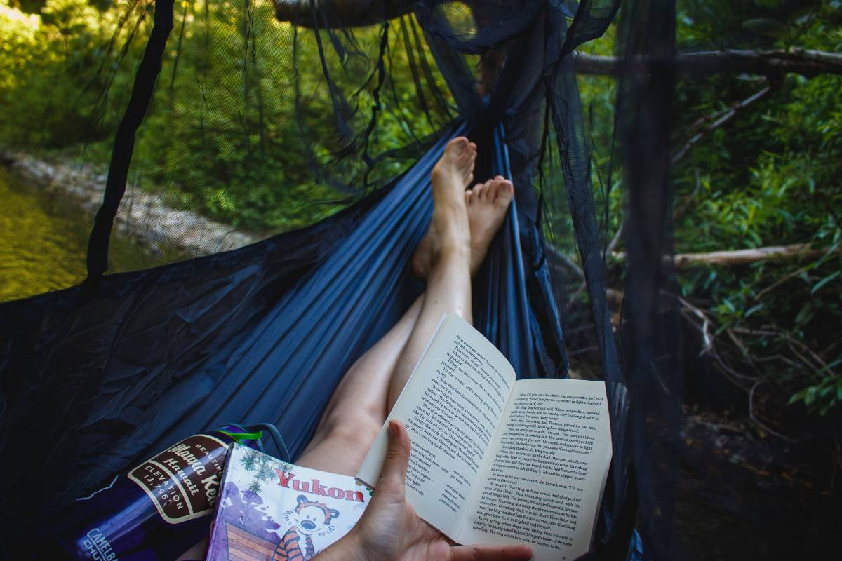 A person reading and lying in a hammock, an item to add to a list of camping must haves, along with additional books and a water bottle in her lap
