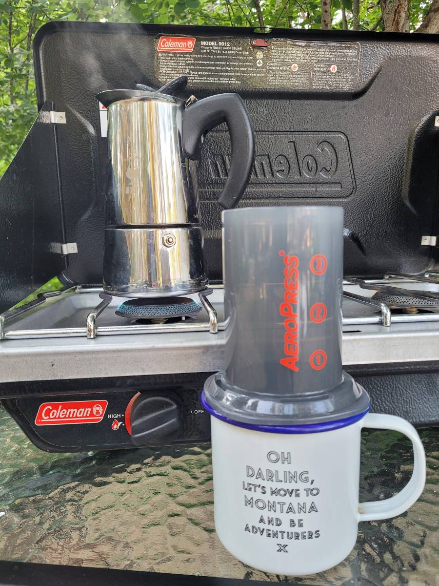 An Aeropress on a coffee mug and a Bialetti Moka Express on a Coleman camp stove, all important camping must haves
