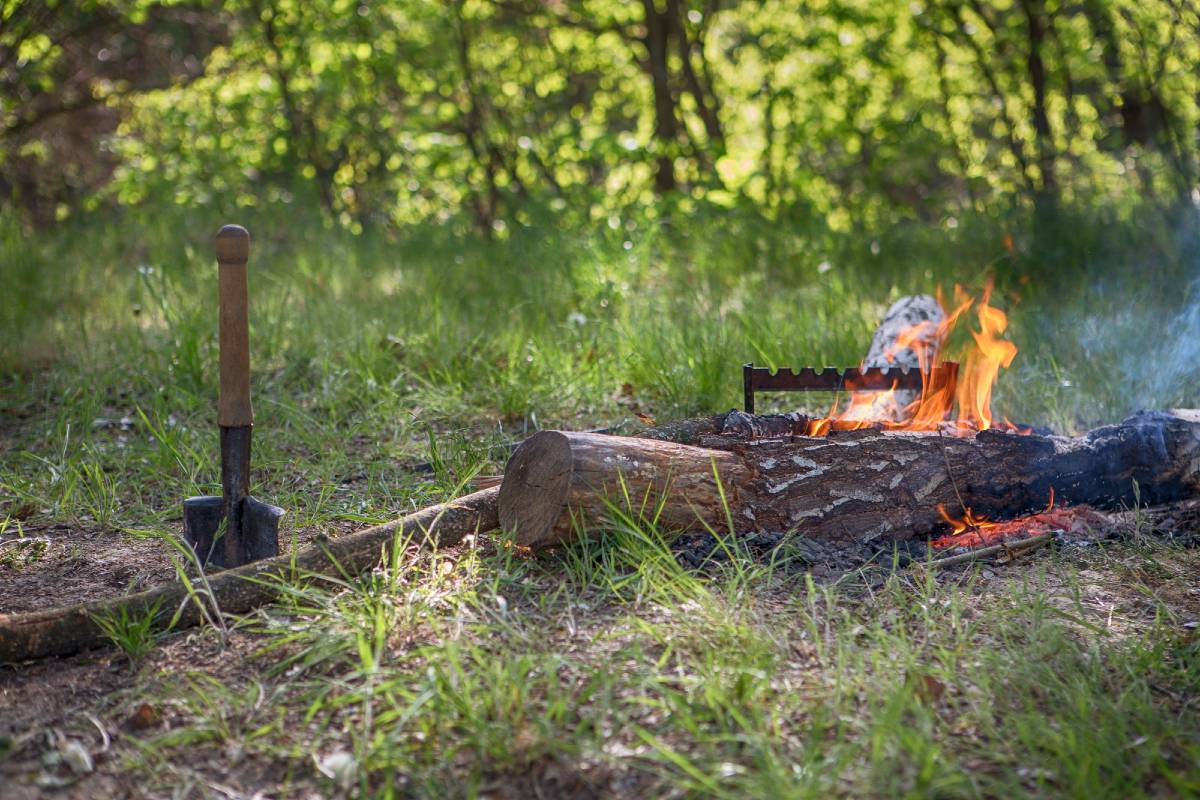 A campfire with spare logs and a shovel in the ground nearby, all camping must haves