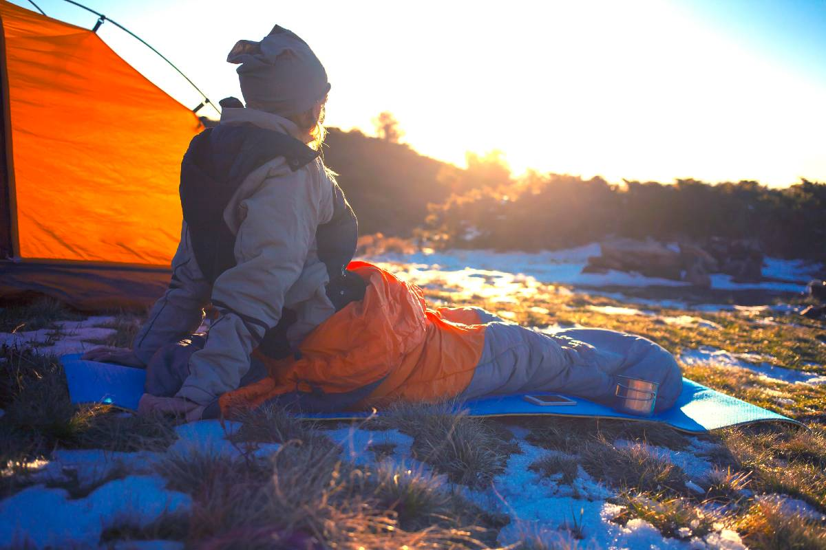A woman sitting outside at sunrise in a sleeping bag on top of a sleeping pad, an item that should be on your camping checklist