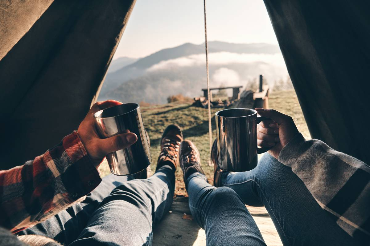Two people lying inside a tent and holding up coffee mugs with a view of outside through their open tent, which is the most important item on a list of camping must haves