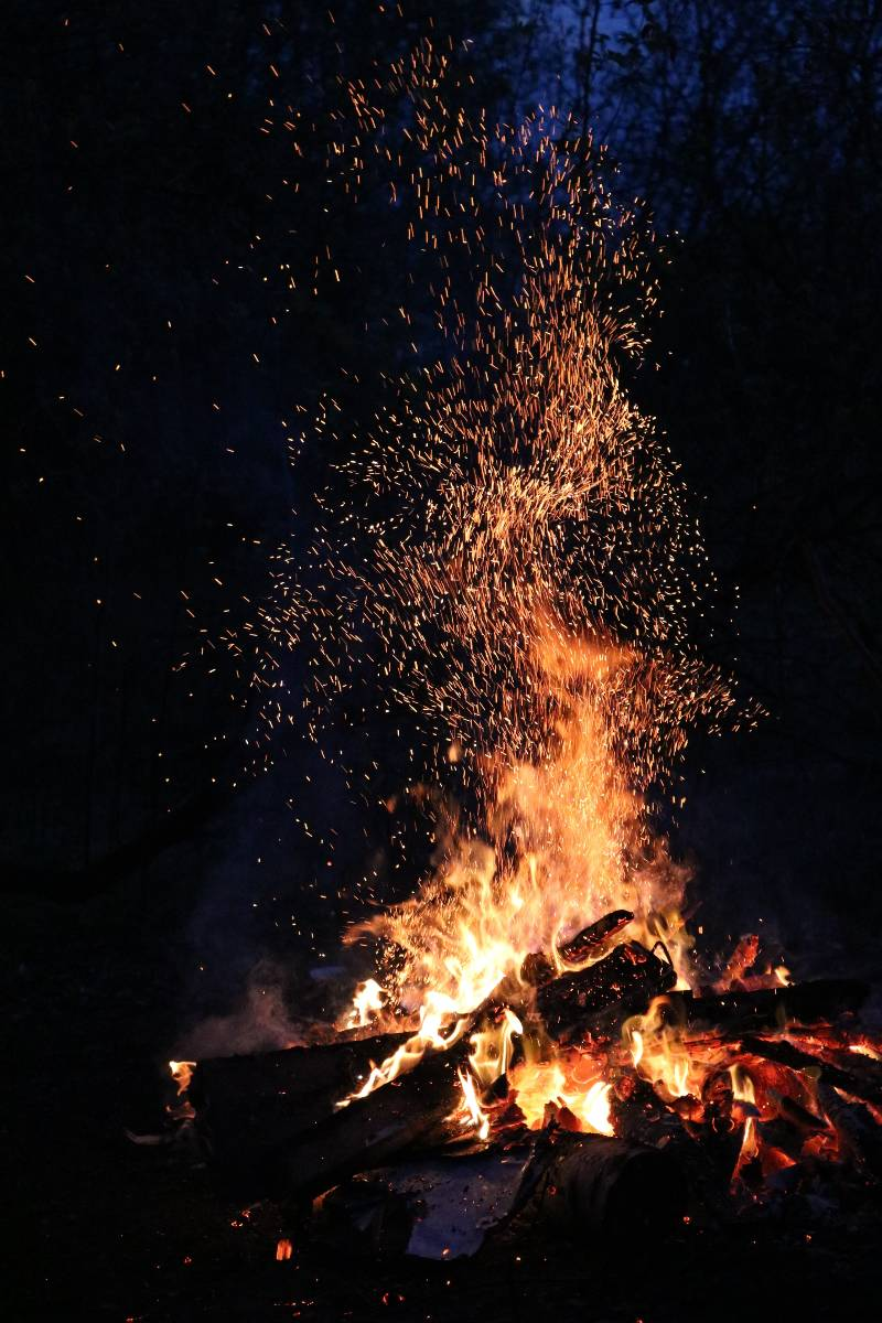 A campfire with embers sparking off at night