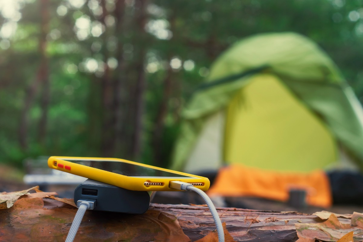 A tent in the background and a cell phone charging on a solar power bank, one of the most useful camping must haves