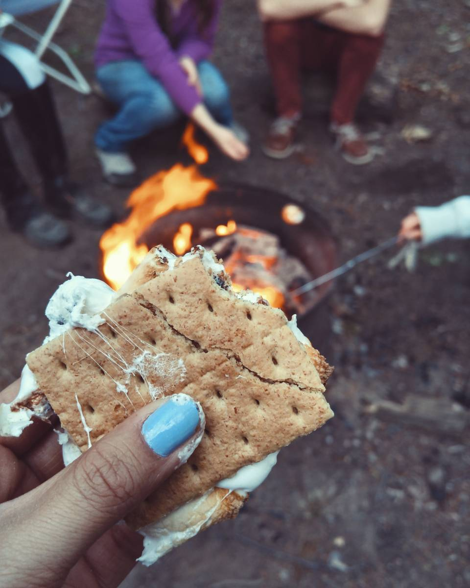 A hand holding a s'more and covered in sticky marshmallow, with a campfire and other campers in the background