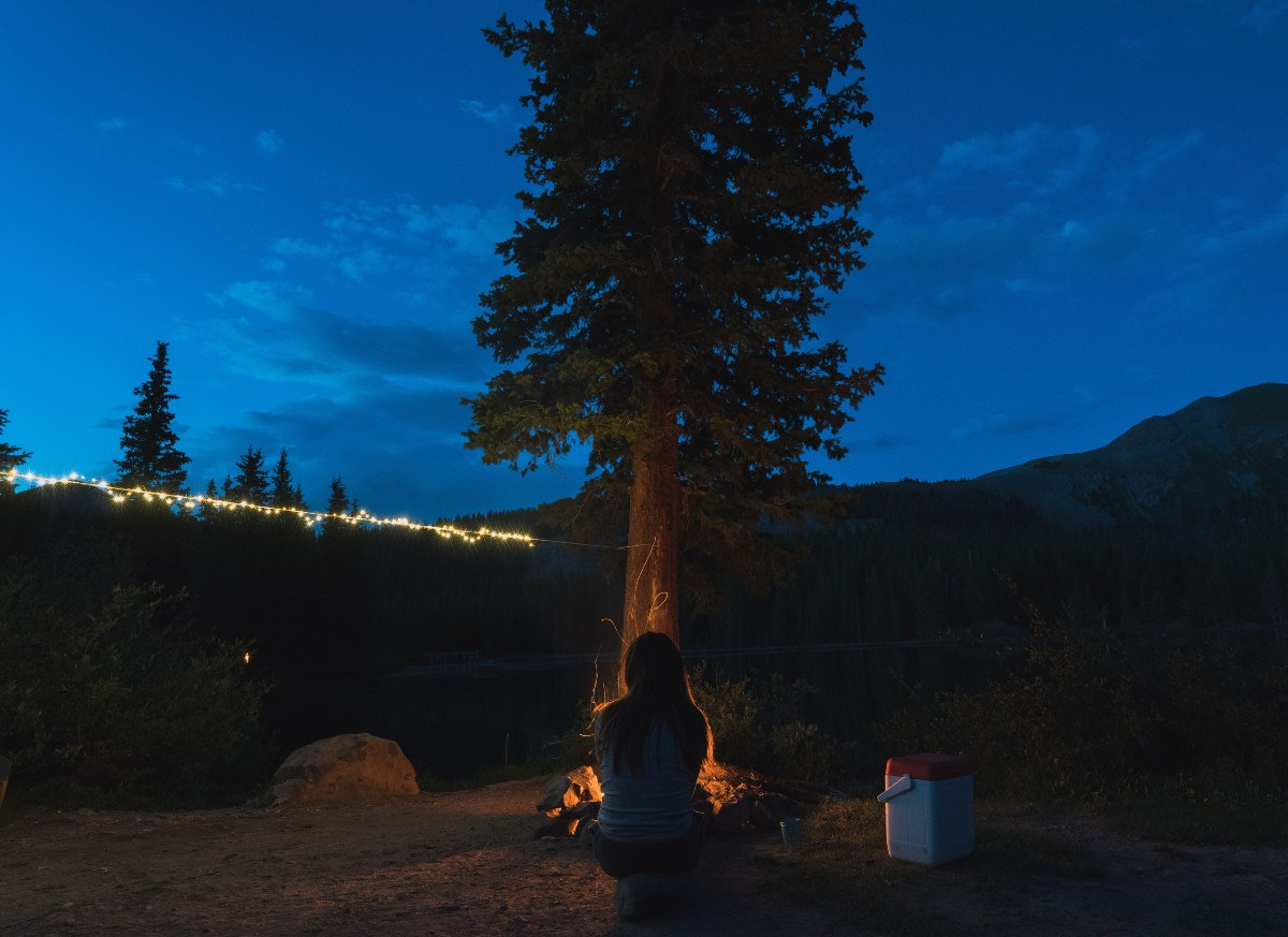 A woman sitting by a campfire near a tree with some top camping must haves, string lights, in the background