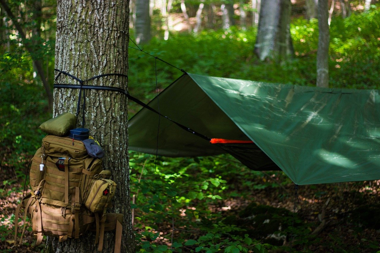 A backpack with gear tied to a tree and a strung-up hammock, one of the most versatile camping must haves