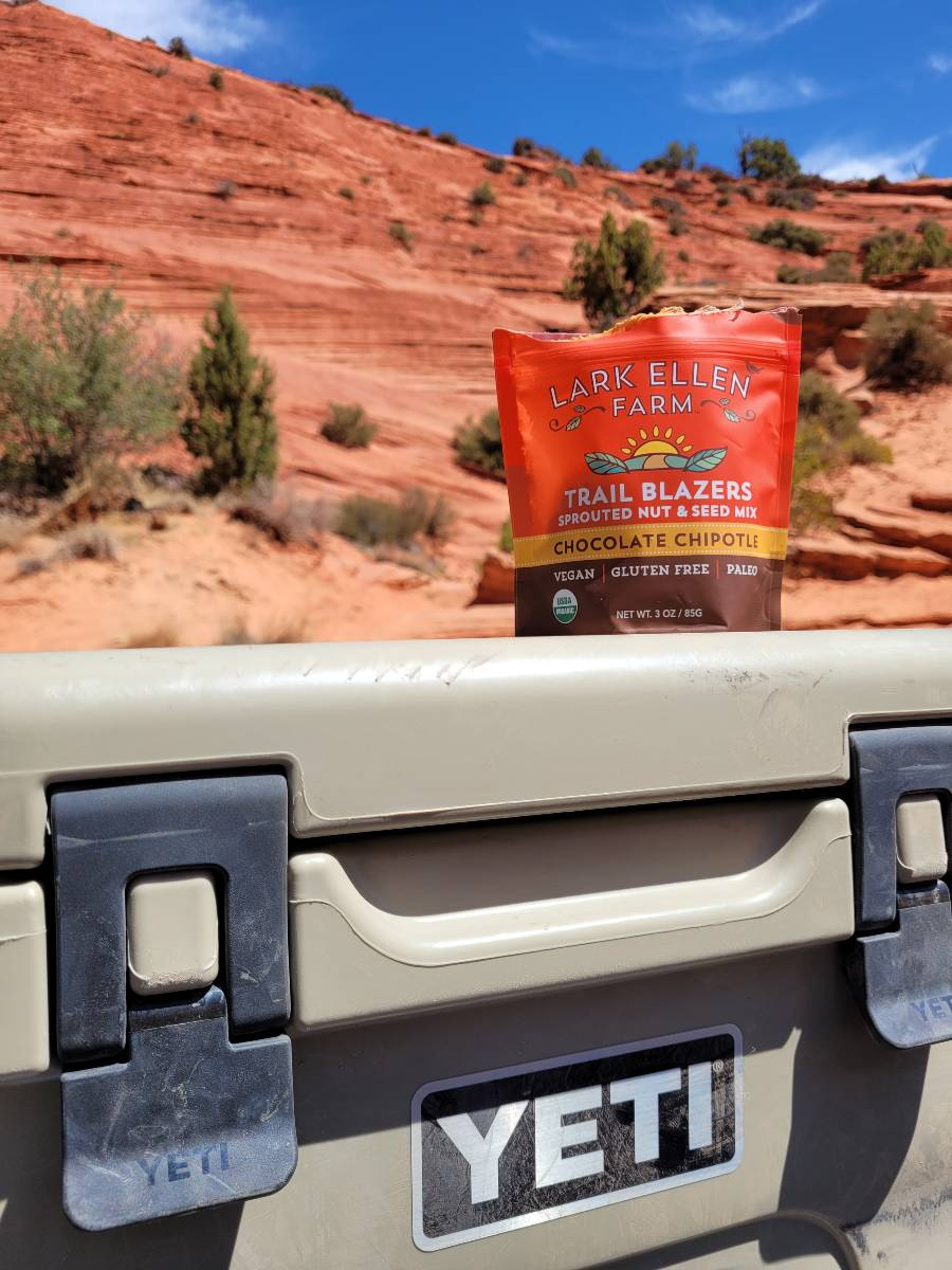 A bag of granola sitting on top of a YETI cooler, one of the most important camping must haves, in front of red rocks in Utah