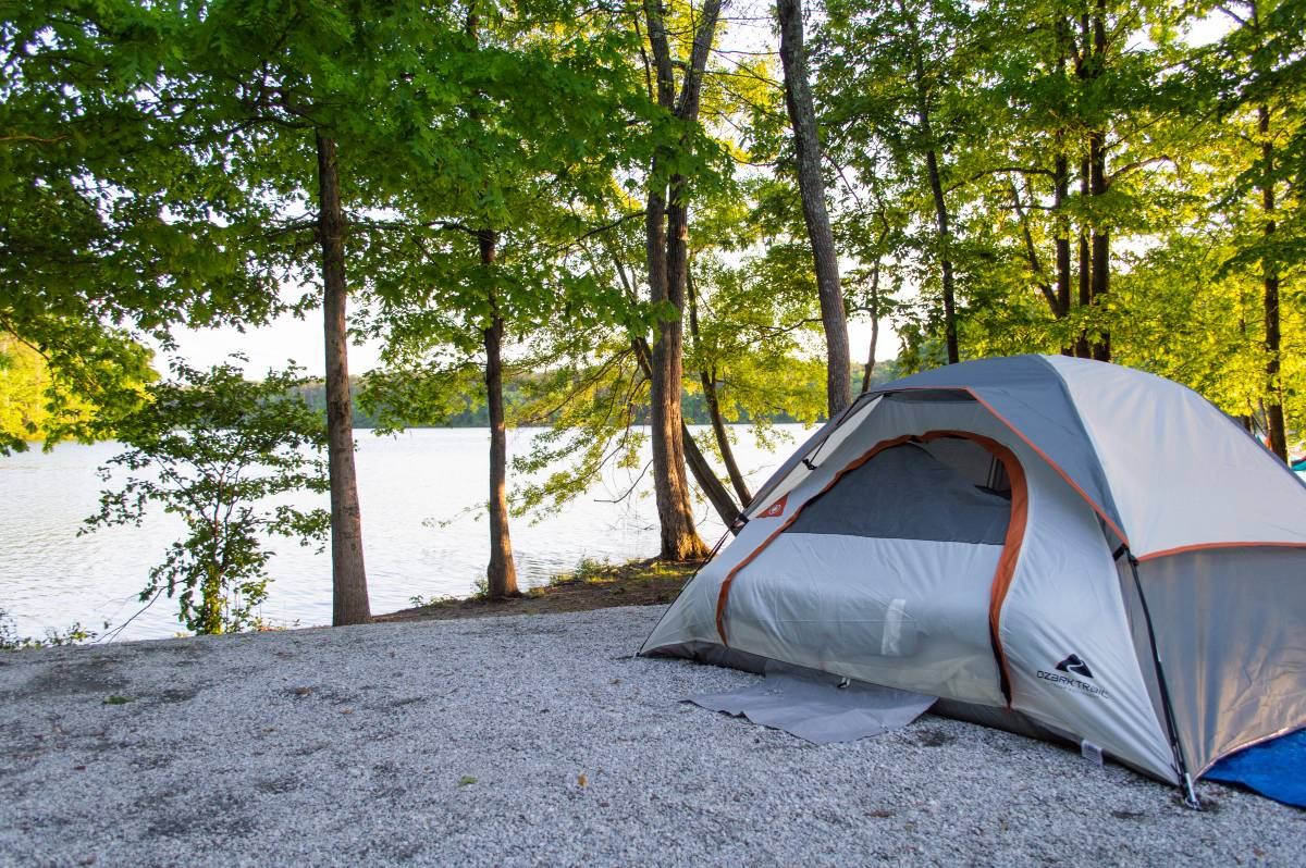 A gray tent pitched near a lake and trees